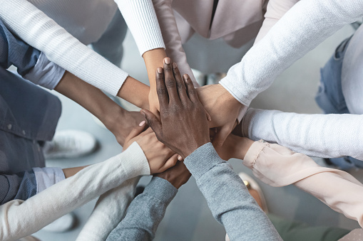 diverse hands in a team circle
